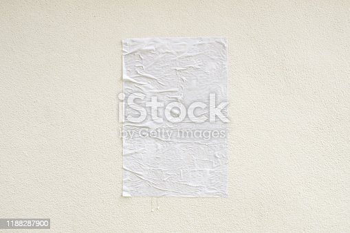 istock Blank white crumpled and creased adhesive street poster mockup on concrete wall background 1188287900