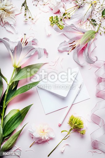 680461500 istock photo Blank white envelop with pencil and various decoration equipment and flowers on pink pale table background, top view 890779782