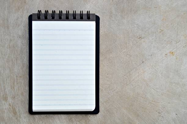 A blank white lined page of a spiral bound vertical notepad with black cover, over a wooden look beige color grungy vintage horizontal background. stock photo