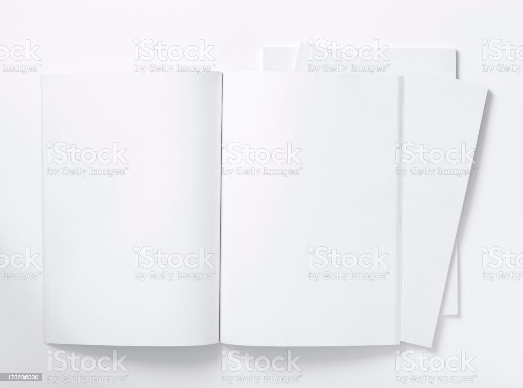 Blank white magazine lying open on a white table stock photo