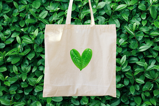 istock Blank white mockup linen cotton tote bag on green bush trees foliage background. Heart logo from leaves. Nature friendly style. Environmental conservation recycling plastic free concept 1135306444