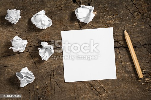 istock Blank white note paper with a pencil and some crumpled papers on wooden surface 1043088934