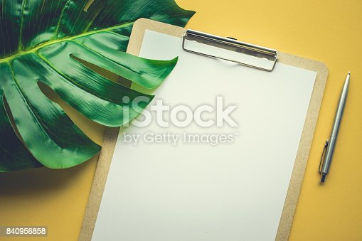 istock Blank white notepaper with tropical leaves laying on yellow table. 840956858