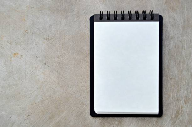 A blank white page of a spiral bound vertical notepad with black cover, over a wooden look beige color grungy vintage horizontal background. stock photo