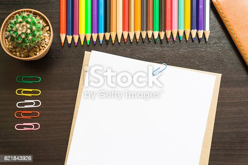 621843818istockphoto Blank white paper and colored pencil on the desk. 621843926