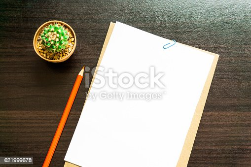 621843818istockphoto Blank white paper and colored pencil on the desk. 621999678