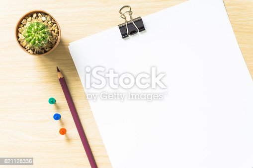 621843818istockphoto blank white paper and pencil on desk 621128336