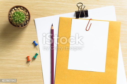 621843818istockphoto blank white paper and pencil on desk 622907542