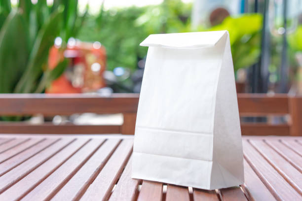 Blank white paper bag for taking out food on a wooden table stock photo