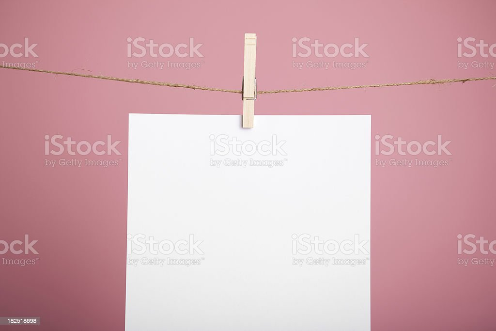 Blank White Paper Hanging on Clothesline over Pink Background stock photo