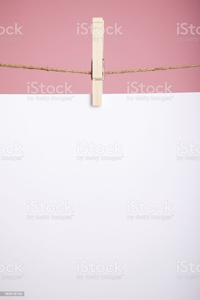 Blank White Paper Hanging on Clothesline over Pink Background royalty-free stock photo