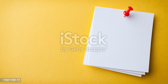 Blank white paper note pad reminder sticky notes on cork bulletin board. Empty space for text. Office equipment.