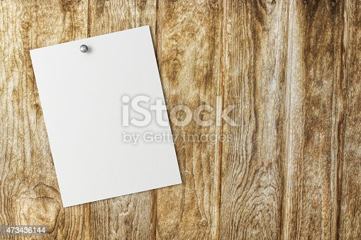 istock Blank white paper on a wood background 473436144