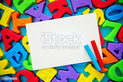 istock Blank white paper on multi colored alphabets background 1180130625