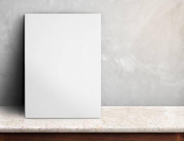 leeres weißes papier plakat auf schwarzen marmortisch an graue betonwand, vorlage für ihr design hinzufügen zu verspotten und raum neben rahmen für mehr text hinzufügen. - stoffregal stock-fotos und bilder