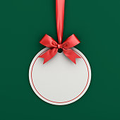 istock Blank white paper round christmas ball frame tag label card template hanging with shiny red ribbon and bow isolated on green background with shadow for christmas decoration 3D rendering 1076812358