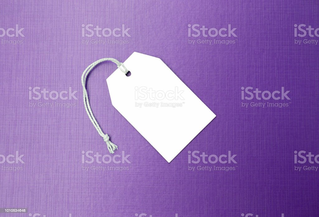 Blank white paper sale tag on purple texture background, business...