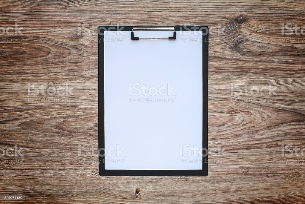 Blank white paper sheet A4 on clipboard. Wooden background. stock photo