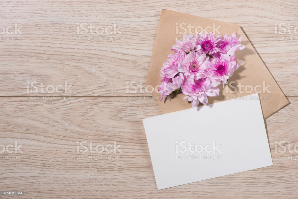 Blank white paper tag with brown envelope and pink flowers on wooden...