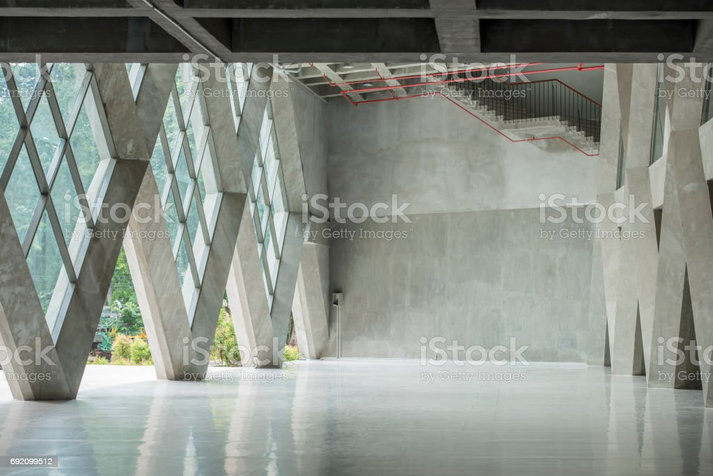 Blank white poster on white wall in empty loft room with concrete floor and big windows mock up stock photo