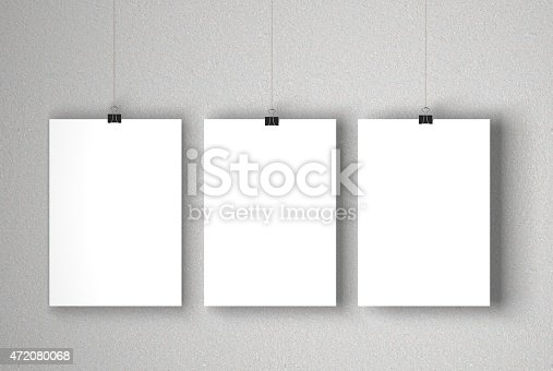 A blank white posters suspended against a grey concrete wall. The paper is being held by a paper clip which is hanging on a piece of string. Light is coming from the left of the image which casts a soft shadow onto the background. The paper is ready for you to add your own designs and artwork.