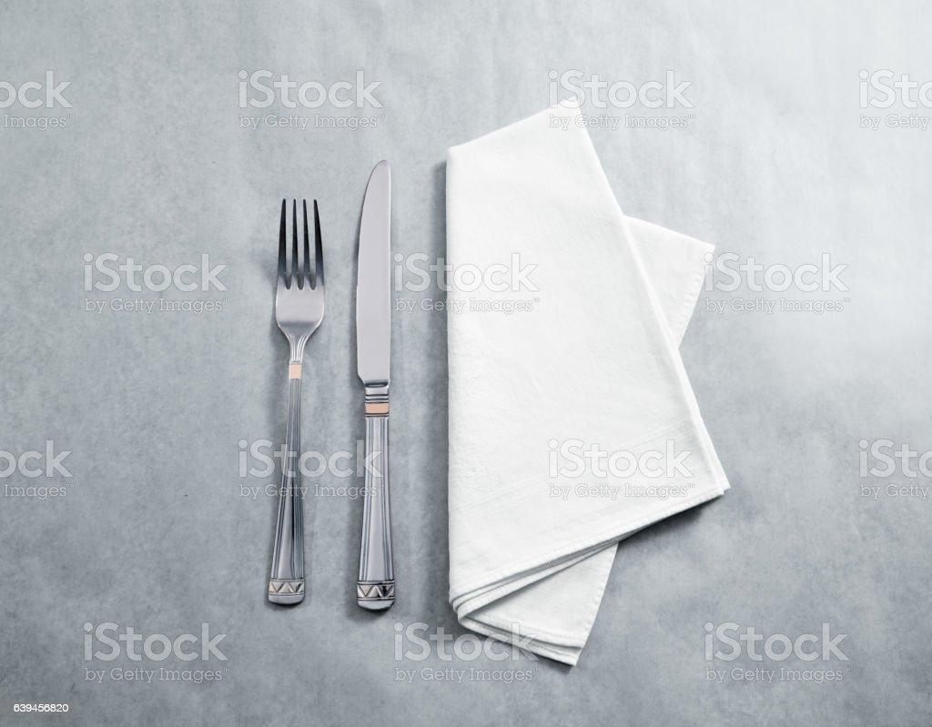 Blank white restaurant napkin mockup with knife and fork
