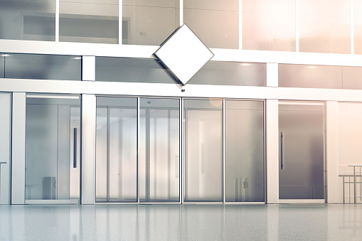 Blank white rhombus signage mockup on the store glass sliding doors entrance, 3d rendering. Commercial building automatic entry, banner mock up. Closed transparent business centre facade, front view.