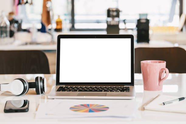 Blank white screen of laptop with headphone, coffee cup, mobile phone and data graph document on the table in kitchen of modern house, business and creative design concept, device for video conference