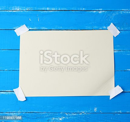 istock A4 blank white sheet attached with adhesive tape to a blue wooden surface 1195937388