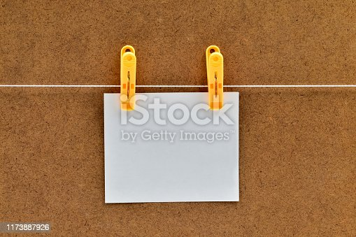 818681972istockphoto Blank white sticker that hangs with a clothespin on a rope on a brown background of chipboard 1173887926