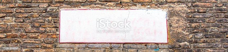 Blank white street sign board panel on brick wall