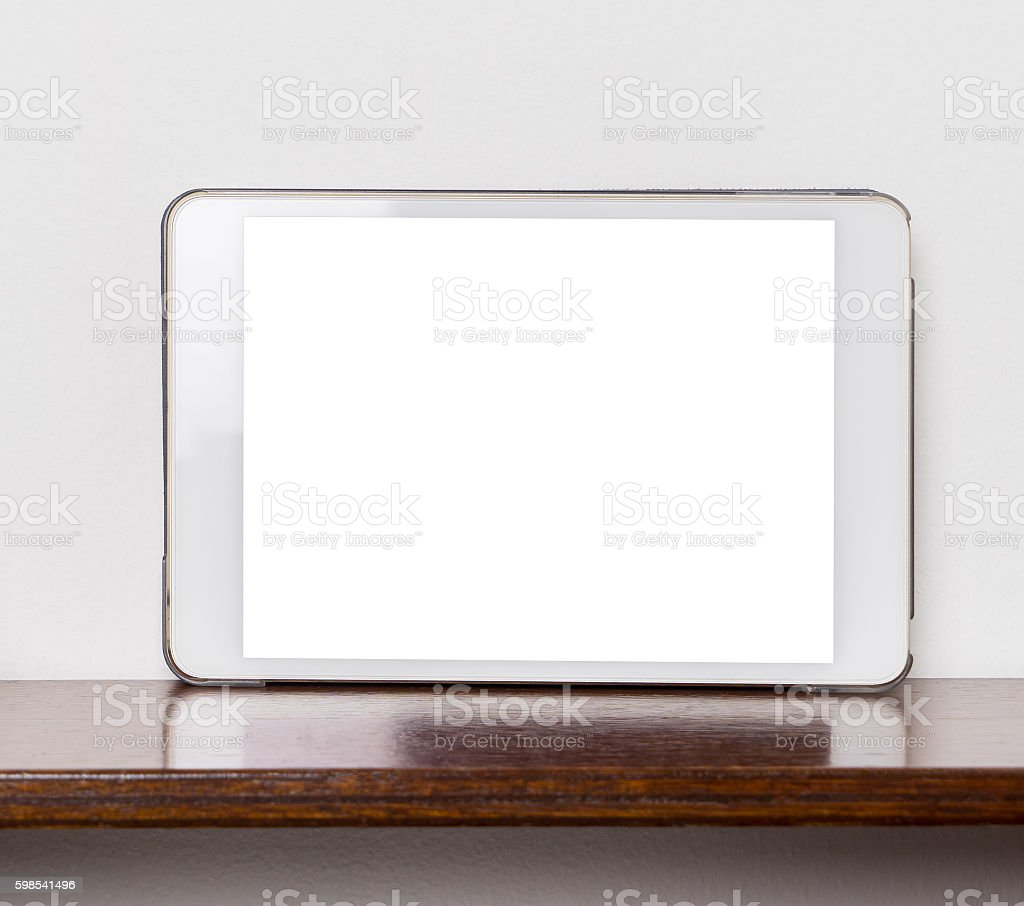 Blank White tablet screen on wooden shelf  with white wall. photo libre de droits