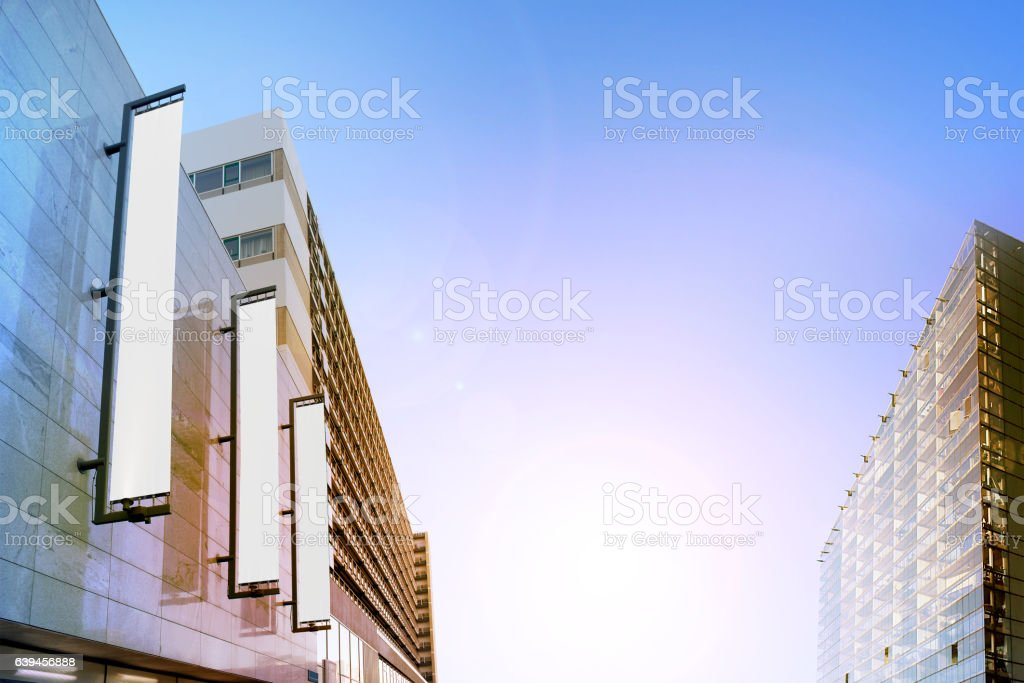 Blank white vertical banners on building facade, design mockup stock photo