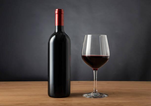 leere Flasche Wein und ein Glas Rotwein auf dem Tisch vor einem dunklen Hintergrund schwarz – Foto