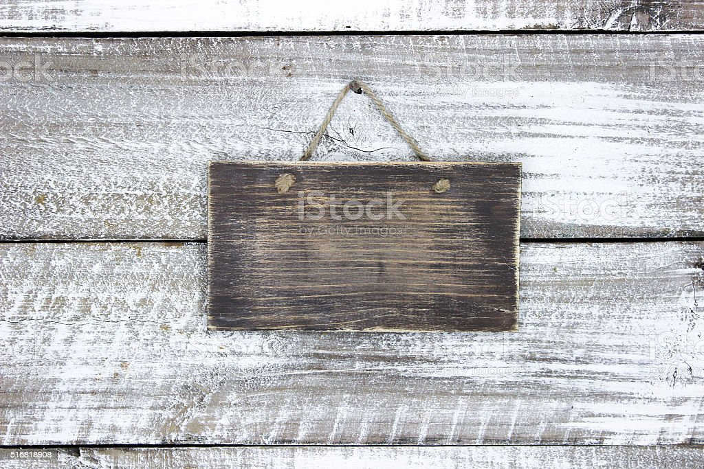 Blank wood sign hanging on rustic door stock photo