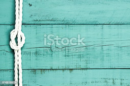 White rope with 8-knot on blank antique mint green rustic wood background