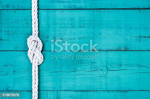White rope with figure 8 knot on blank antique teal blue rustic wooden background