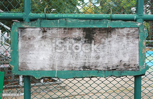 istock Blank wooden label on steel wire mesh fence. 995905906