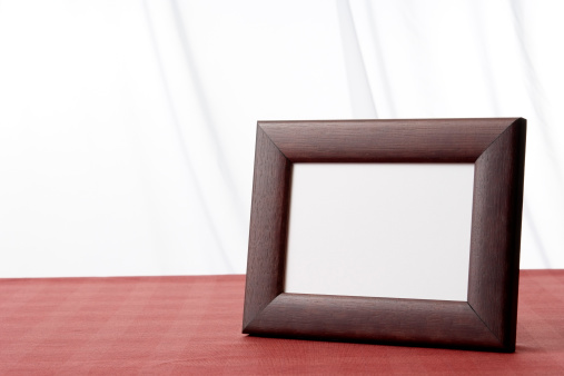 Blank brown wooden picture frame on the table in front of white curtain with copy space.