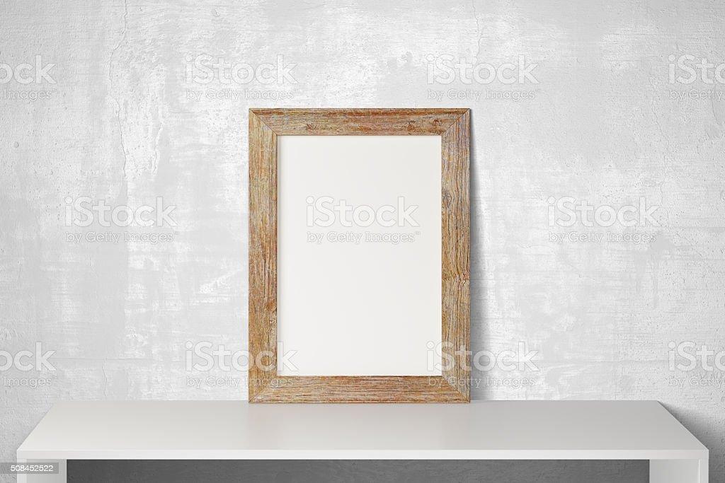 Cadre photo en bois vide sur blanc tableau et de béton étage