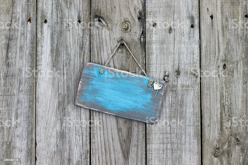 Blank worn blue sign hanging on wood fence stock photo