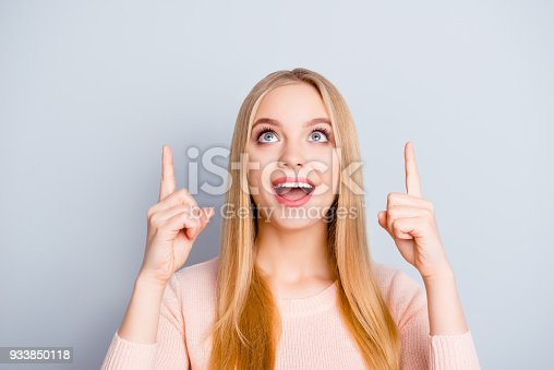 Blank wow omg way empty people surprise person concept. Close up portrait of cute sweet astonished wondered amazed shocked beautiful pretty charming girl pointing up isolated gray background copyspace