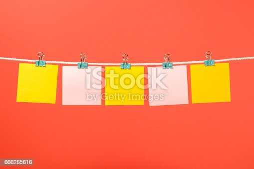 istock Blank yellow and pink paper notes on the string over color background 666265616