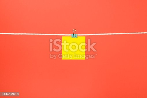 istock Blank yellow paper note on the string over color background 666265618