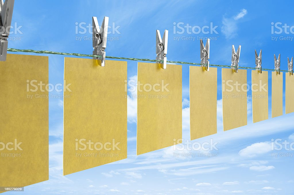 Blank yellow post it notes drying on a clothes line royalty-free stock photo