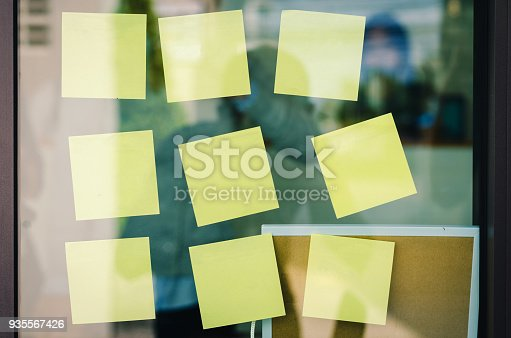 istock blank yellow sticky note or post note stuck on glass wall. 935567426