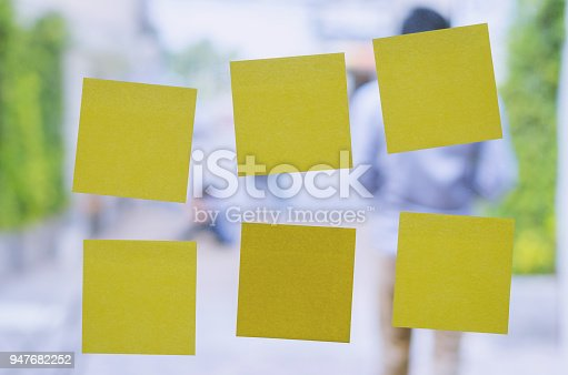 istock blank yellow sticky note or post note stuck on glass wall. 947682252