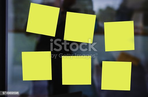 istock blank yellow sticky note or post note stuck on glass wall. 974969598