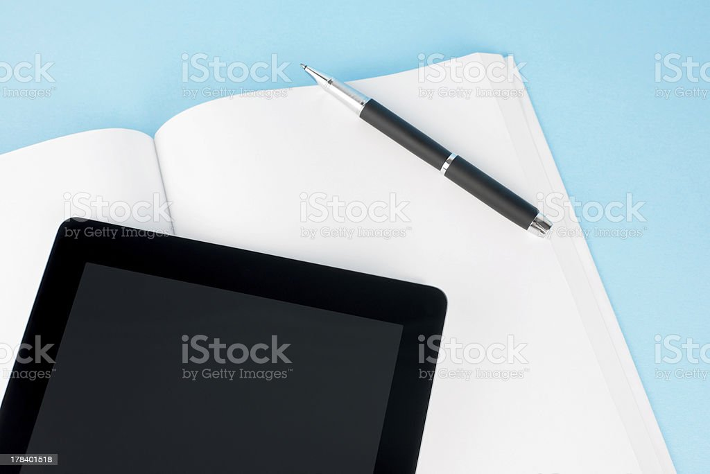 Blank/empty white book,pen and tablet on light blue Background.