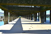 View from the sandy beach under concrete pier in front of the sea.. Pillars, break water covered by moss and algae. Diminishing perspective. Right side pier entrance harbor sailing boats and fisher ships. Pier constructions limits with other city \